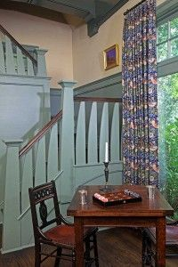 This spot, adjacent to the staircase up to the library, is an inviting place to play cards or board games. The drapery fabric is Morris's 'Strawberry Thief.'  Standen Still: English Arts & Crafts in Rural Virginia