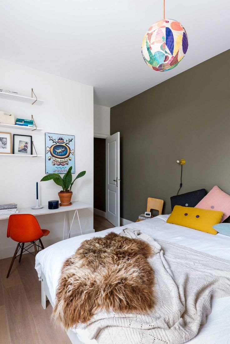 Bedroom with green wall and colorful Hay pillows
