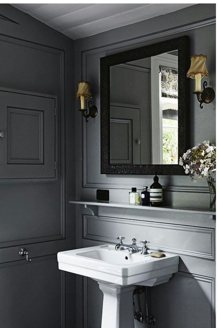 Small shelf above sink - in fabulous bathroom or powder room with gray walls, beautiful mouldings and a white pedestal sink.