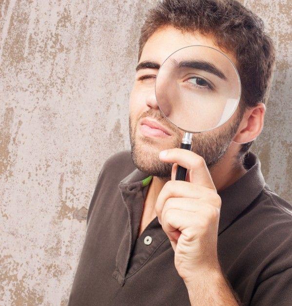 Hombre con una lupa en su cara Foto Gratis