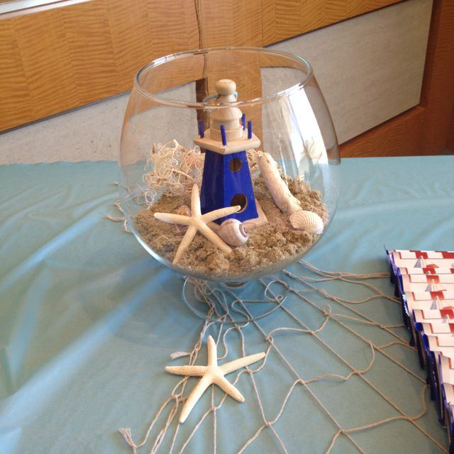 sand, starfish, light house in a glass vase