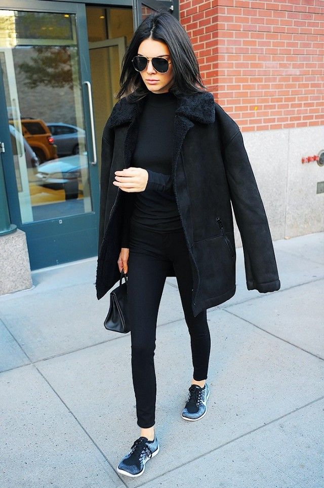 Kendall Jenner wears a turtleneck, suede shearling-lined jacket, skinny jeans, Nike sneakers, aviator sunglasses, and a mini Birkin bag