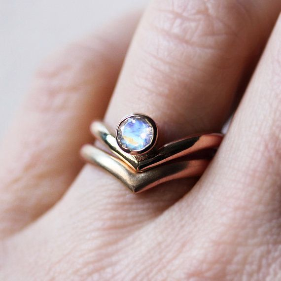 This stunning rose gold ring set features a 5mm round rainbow moonstone that glows with an otherworldly light. This modern engagement ring set is