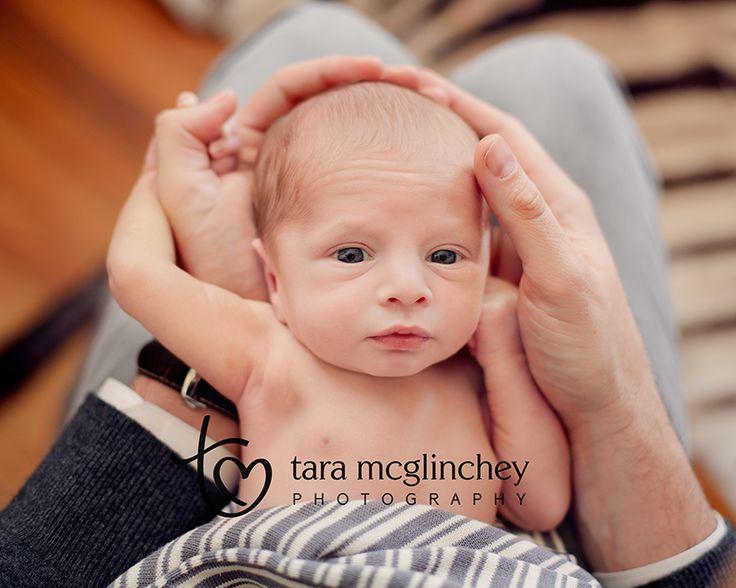 Newborn baby in dads hands for manhattan newborn photographer tara mcglinchey www taramcglinchey