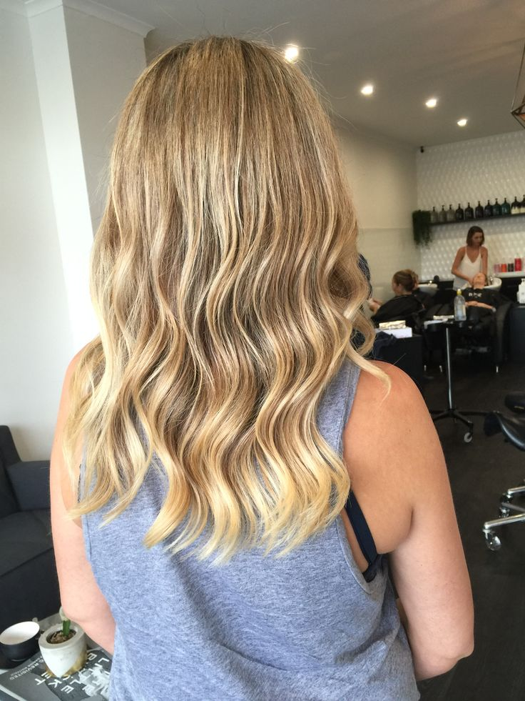 Honey and cream tones, freehand painting and balayage with a tonged wave
