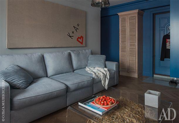 Вид из гостиной на зону прихожей. Диван RoyBosh. Деревянный шкаф, сделанный на заказ, выгодно оттеняет насыщенный синий цвет стены.