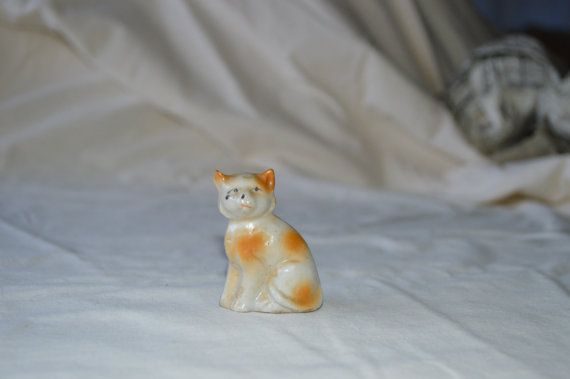 White and orange porcelain cat. Made in Japan. 2 high x 1 1/2 wide    Has a couple of black marks on face and two blemishes from manufacturing