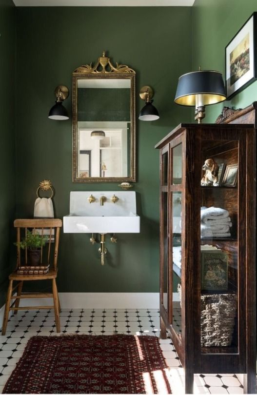 Green color, mirror, light fixtures, and curio for…