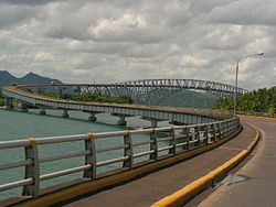 The San Juanico Bridge, view from Samar, towards Leyte.  On July 2, 1973, the 2.16-kilometer long San Juanico Bridge, the longest bridge in the Philippines spanning a body of sea water between the islands of Samar and Leyte in the Visayas, was inaugurated. The San Juanico Bridge is part of the Pan-Philippine Highway (also known as the Maharlika Highway). Its longest length is a steel girder viaduct built on reinforced concrete piers, and its main span is of an arch-shaped truss design. The…
