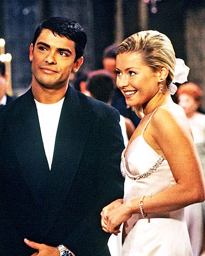 All My Children's Hayley Vaughan  Kelly Ripa and her husband Mark Conseulos got to tie the knot twice—once in real life, and once as Hayley Vaughan and Mateo Santos on All My Children. For the couple's 2000 TV wedding, the bride wore a form-fitting satin gown with crystal detailing.