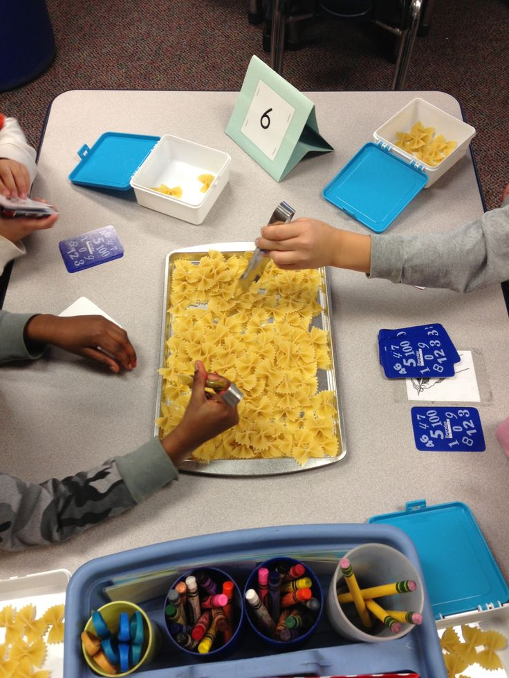 Kindergarten fine motor math center: flip over a number card and grab that many noodles with tongs.