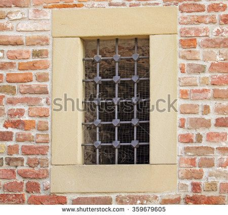 Iron bars on the stone fortress wall  - stock photo