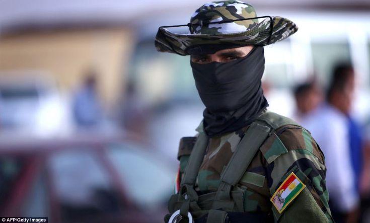 an iraqi kurdish security guard waits to check the id cards of iraqi