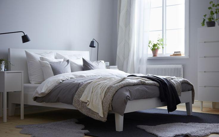Ein Schlafzimmer mit NORDLI Bettgestell in Weiß, FÄRGLAV Bettwäsche-Sets in Grau/Weiß, NORDLI Ablagetischen in Weiß und SVEIO Kommode mit 5 ...