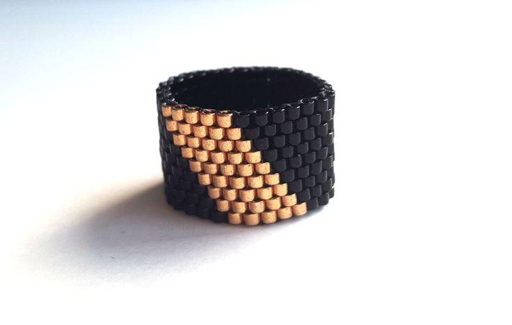 Questo anello è fatto a mano con perline di alta qualità miyuki delica, utilizzando colori: nero e oro.  È mano tessuta, laggiunta di perline uno per uno. Questo anello è leggero e molto comodo da indossare.  Larghezza: 1,2 cm (0,47 pollici)  Posso rendere questo anello qualsiasi formato che ti piace.  Grazie per aver visitato il mio negozio!  Per saperne di più dei miei oggetti fatti a mano: https://www.etsy.com/nl/shop/MarMosa?ref=hdr_shop_menu