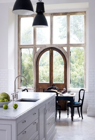 Windows, arched door way, wood, & white kitchen and casual dining