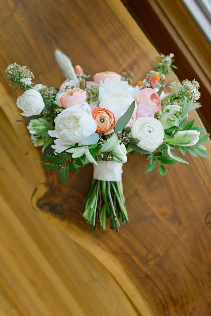 loose bridal bouquet of white peony, peach roses, white ranunculus, rosita vendela roses, white scabiosa, white majolik spray roses, bunny tail grass, pink rice flower, peach ranunculus, scabiosa pods, white spirea, white parrot tulips, elm & seeded eucalyptus wrapped in cream satin ribbon
