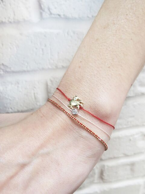 Subtle and chic, this red string RedLine bracelet is enlaced in a gold chain that sparkles. Perfect for everyday stacking.  Handcrafted in 18-karat yellow gold. Bracelet adjusts from 6-in. to 6 1/2-in. long. Three linked bracelets make the bracelet adjustable.