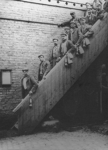 Miners posed on a stairway at the Gibfield Colliery, Atherton, 1907.