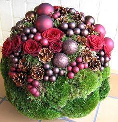 Kerstbal maken met bruine en rode tinten in kussentjesmos en met kleine kerstballetjes.  Alternatief: met mos en vetplantjes en donkerrode of paarse balletjes