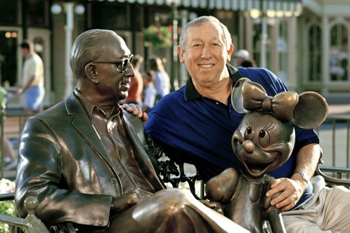Roy E. Disney posing with the Friends statue of Roy O. Disney and Minnie Mouse.