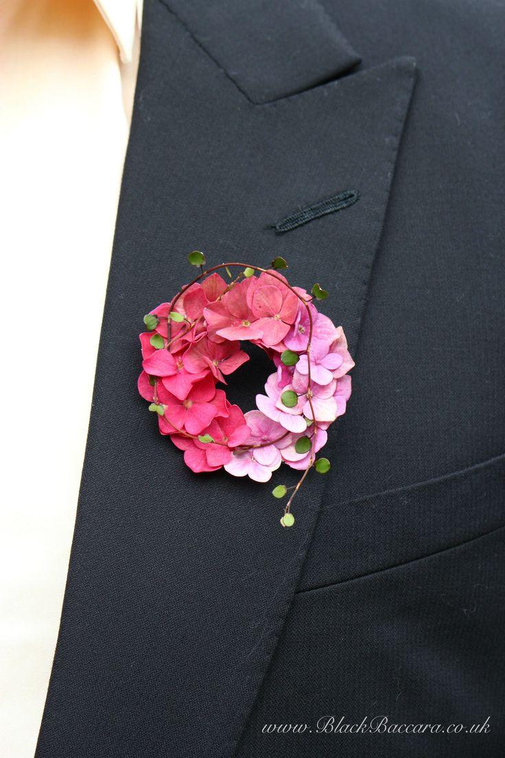 Soft pink hydrangea boutonniere with trailing muehlenbeckia vine…