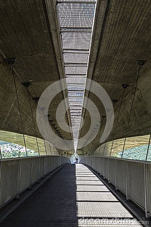 Pedestrianized road is beneath motorway, coupled concrete and steel.