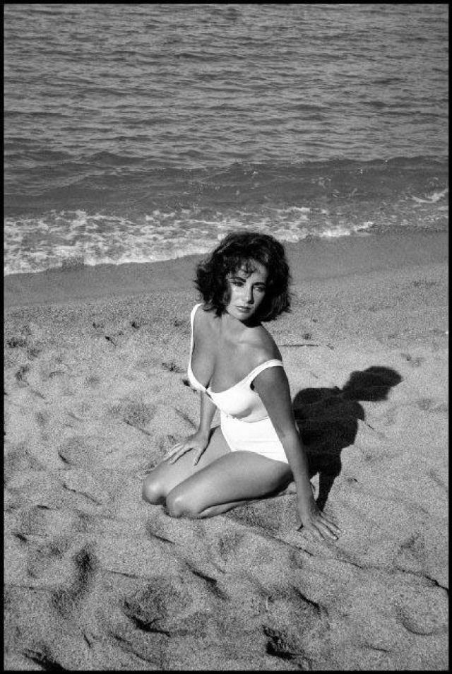 "Spain. Sagaro. 1959. Twenty-five-year-old Elizabeth Taylor on the set of ""Suddenly Last Summer"", in which she co-stars with Katharine Hepburn and Montgomery Clift. It is Taylor's first film after the death of her 3rd husband, Mike Todd, in a plane crash. , 1959  by Burt Glinn  Photograph"