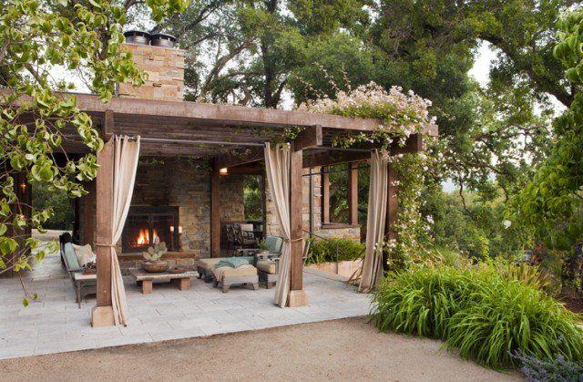 pergola avec rideaux -taupe-terrasse-carrelée-plantes-grimpantes-cheminée-extérieur