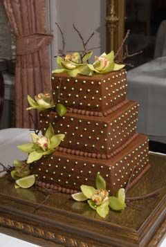 Three tier square chocolate brown wedding cake. A chocolate covered mud cake is garnished with stunning green cymbidium orchids