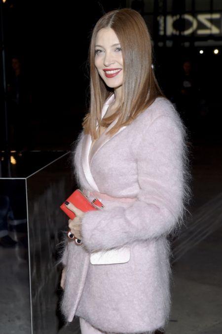 Ada Fijał w jasnoróżowym garniturze z czerwoną kopertówką