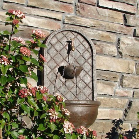 A prime example of exquisite craftsmanship, the Milano Outdoor Wall Fountain features an antique brass spout from which the water flows gently before falling into a small basin. The basin overflows at #landscapearchitecturecourtyard