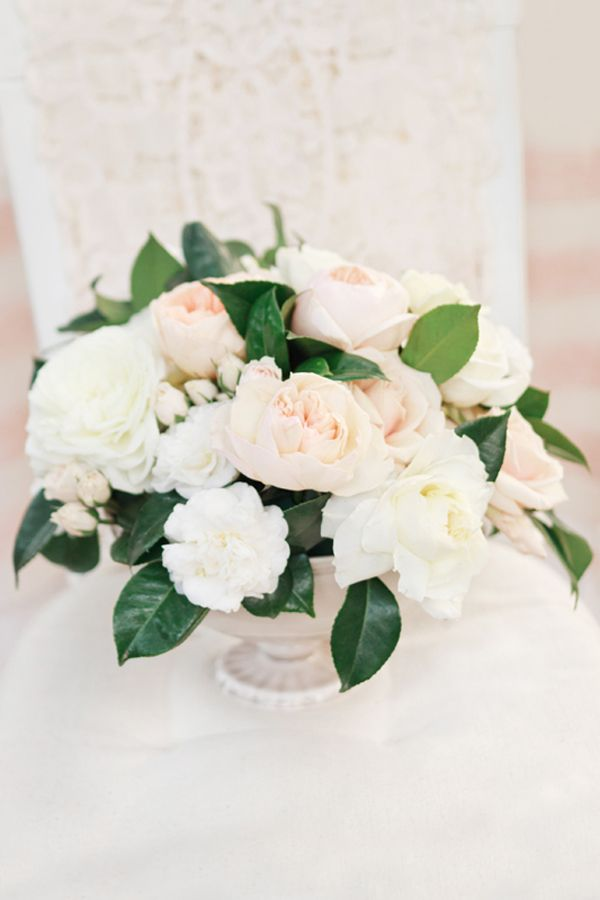 Lovely blush and cream centerpiece, accented with Camilia leaves. #wedding #flowers