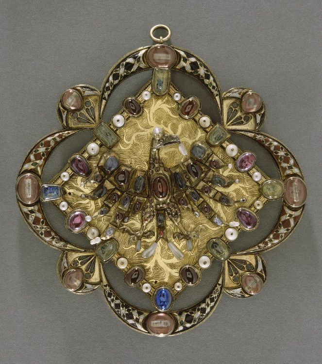 This jewel reliquary was probably made in Prague in the middle of the 14th century. It was used to tie the tails of a ceremonial garment. Relics it contained gave the wearer prestige and protection. Luxury materials and care taken in its implementation suggest that this is an imperial order. Set with precious stones and enriched with enamel, it represents crowned eagle on background of flames, emblem of Bohemia. Source…