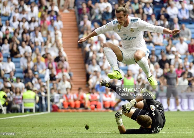Real Madrid's Welsh forward Gareth Bale (top) jumps over Levante's goalkeeper Raul Fernandez during the Spanish Liga football match Real Madrid vs Levante at the Santiago Bernabeu stadium in Madrid on September 9, 2017. #realmadrid