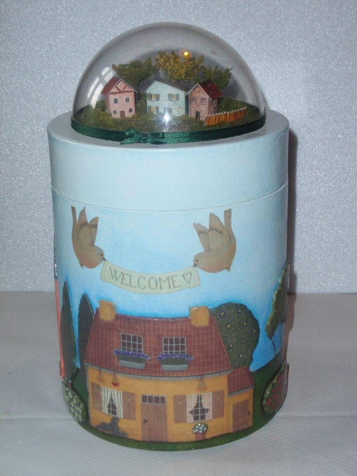 Barattolo in cartone decorato a decoupage 3D piatto su sfondo dipinto a mano e sul coperchio casette e alberi creati a mano