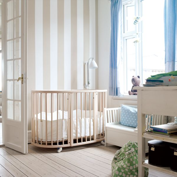 thoughtful, layered neutrals and soft pops of color make this Stokke Sleepi  nursery a stunning space