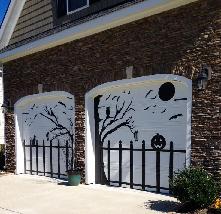 halloween garage door decorated using black contact paper with tree fence bat