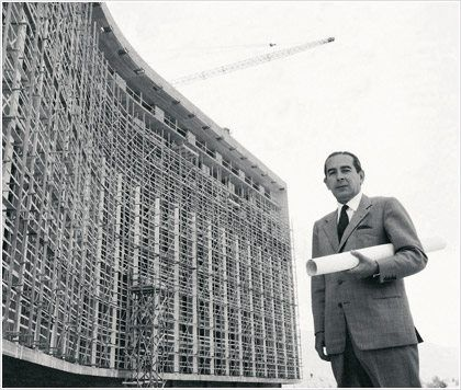 """1958: Architect Emmanouel Vourekas in front of the (under construction) """"Athens Hilton"""" hotel"""