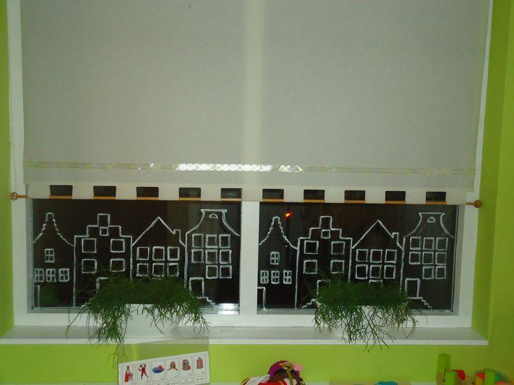Raamversiering grachtenpandjes. Met witte plakkaatverf op de binnenzijde van het raam getekend. Leuk voor de sinterklaas- en kersttijd.