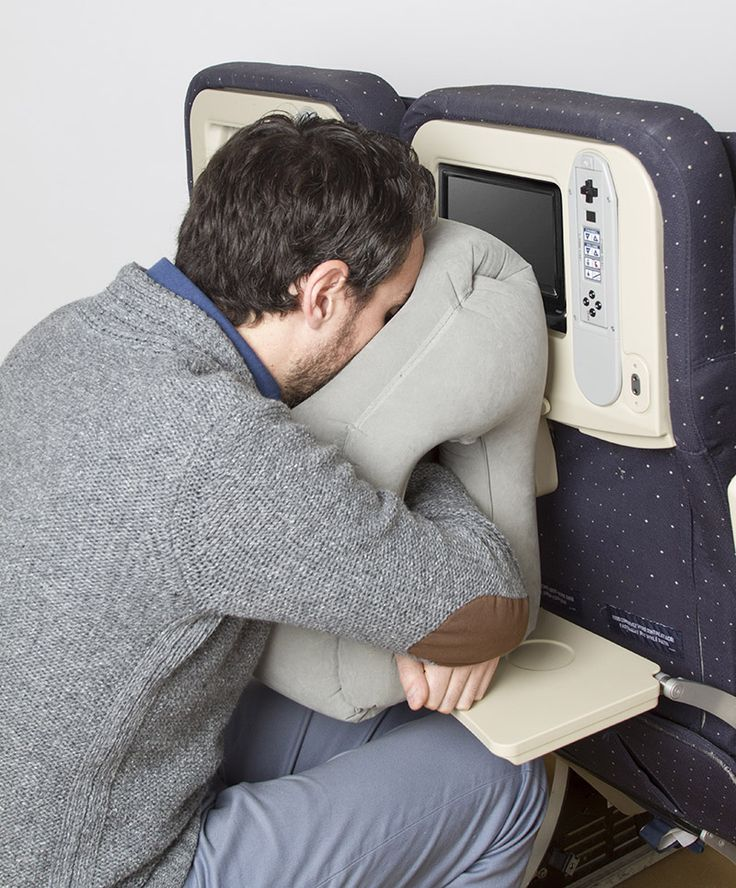 Woollip Travel Pillow.  Inspired by the design of portable massage chairs, the inflatable pillow rests on the seat-back tray, and allows you to slide your arms through it, while resting your head in the face support, much like on a massage table.