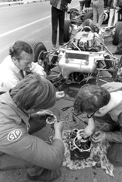 Colin Chapman watches the Lotus Team mechanics, rebuilding the transaxle at the Belgian Grand Prix in 1968
