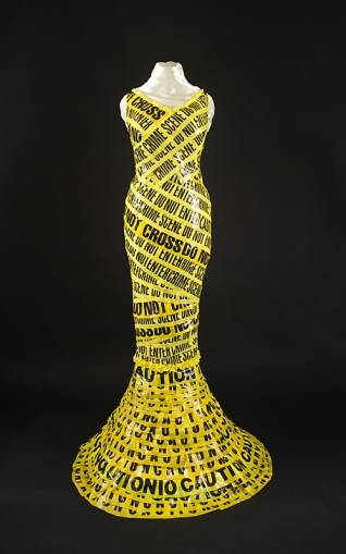 """Police tape is fashioned into """"warning-wear"""".    Tape from police crime scenes across the west, cover a dress made from torn table cloths. This cautionary costume took 50 hours to create and was completed in 2011.Scientists estimate that everyone alive today carries within her or his body at least 700 contaminants."""