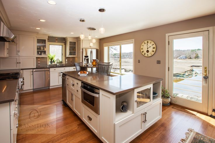 This transitional style kitchen design is a bright spot at the center of this home with soft white flat panel cabinetry.  It is accented by a Ceasarstone quartz Lagos blue countertop and a gray backsplash in frosted glass with glass mosaic blend accents.  The L-shaped island includes a floating table.  Glass front upper cabinets and open shelving in the island leave space for display and contribute to the airy atmosphere.  Photos by Susan Hagstrom