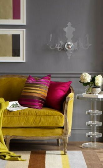 Mustard Couch With Magenta Accent Pillows Against A Grey