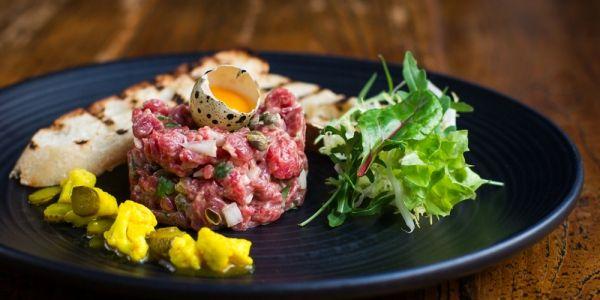 Dit recept voor steak tartaar van restaurant South of Houston in Den Haag is pietje precies. Het is even pielen met de grammen, maar dan heb je ook e...