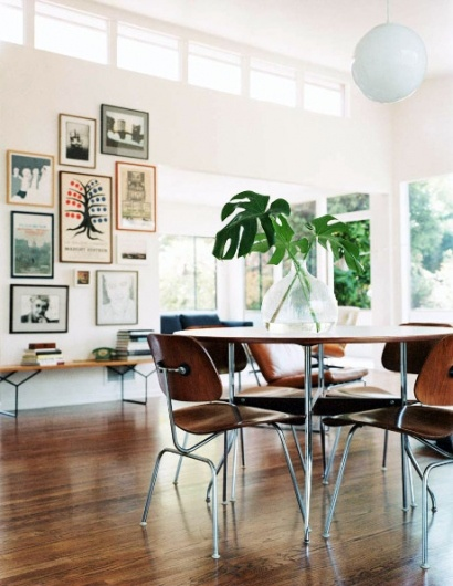 Dining area with dark wood floors, white walls and lamp, natural greenery and cool picture collection on wall