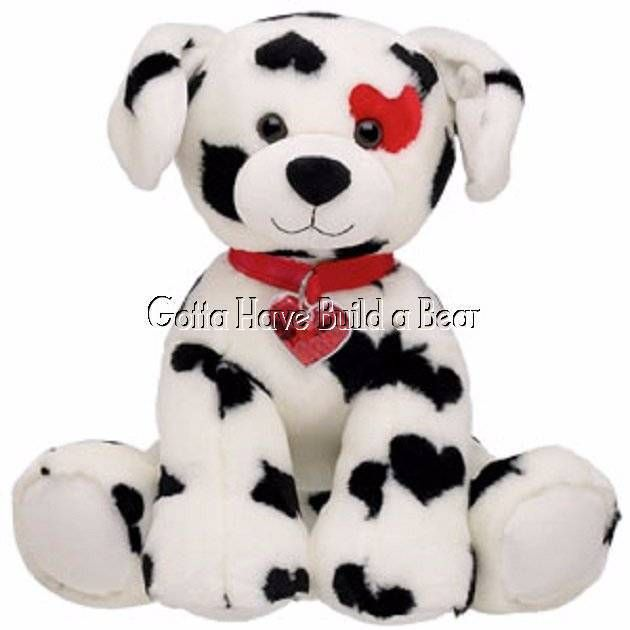 """This adorable 15"""" pup is white with all-over black hearts, a red heart on it's eye and a red collar with a bubble heart charm and floating red hearts inside. """"A person should be judged not by their mistakes but by their willingness to rectify their mistakes."""". 