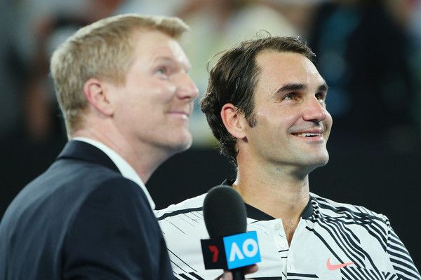 Roger Federer Photos Photos - Roger Federer of Switzerland looks up at the video screen with Jim Courier after winning in his fourth round match against Kei Nishikori of Japan on day seven of the 2017 Australian Open at Melbourne Park on January 22, 2017 in Melbourne, Australia. - 2017 Australian Open - Day 7