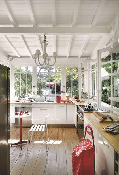 Une cuisine lumineuse installée dans la véranda de cette maison de pêcheur
